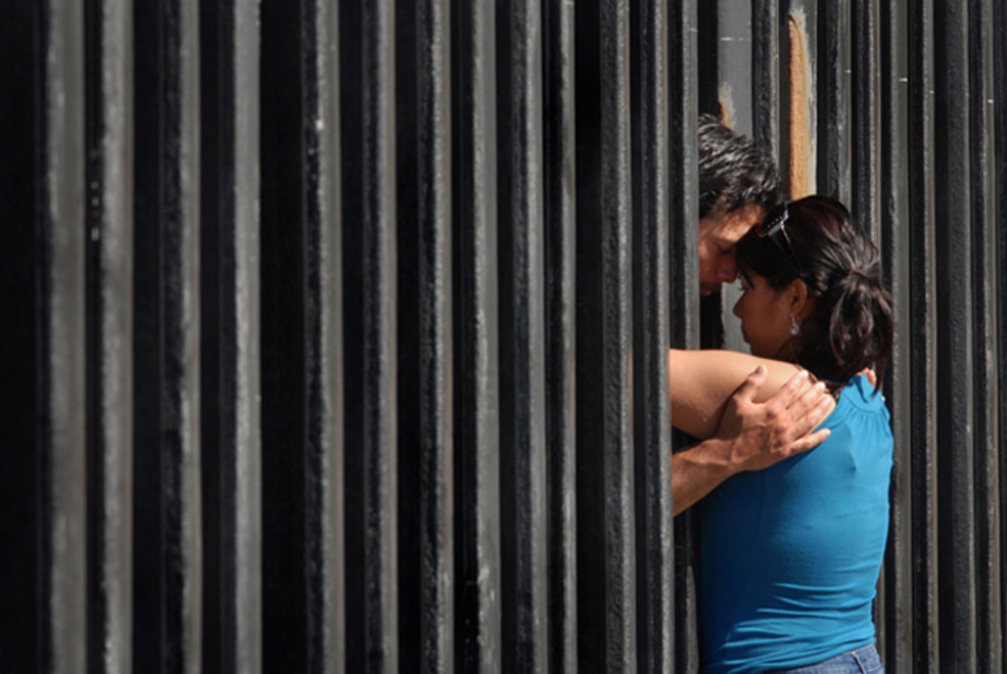 Two people embrace at the border fence separating Mexico and the United States.