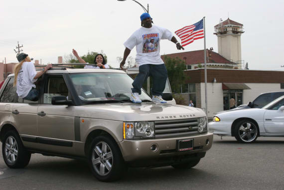 "J-Diggs ghost riding a Range Rover on the set of the 2006 music video shoot for E-40's ""Tell Me When To Go."""