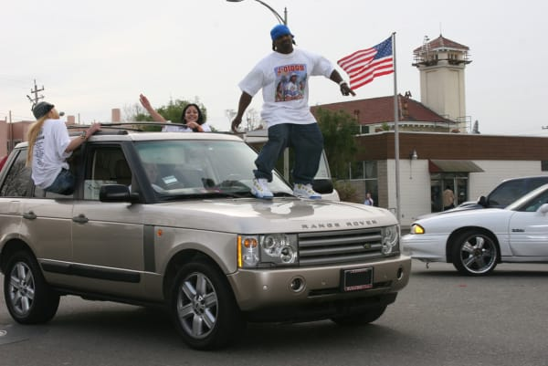 """J-Diggs ghost riding a Range Rover on the set of the 2006 music video shoot for E-40's """"Tell Me When To Go."""""""