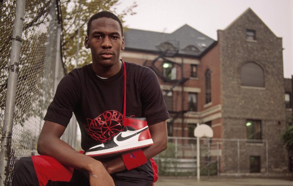 Michael Jordan with an original Air Jordan 1 over his shoulder.