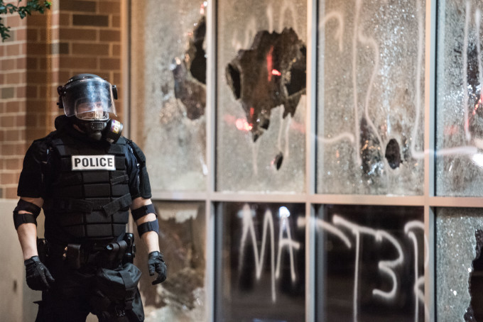 Police officer in riot gear in front of vandalized storefront.