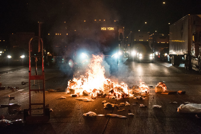 A fire set by protesters burns near a bus on the I-85 (Interstate 85) during protests