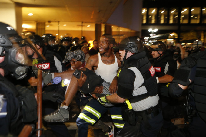 Police and protesters carry a wounded demonstrator.