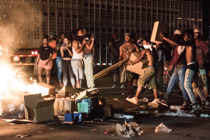 Protesters tossing cargo from tractor trailers onto a fire on I-85