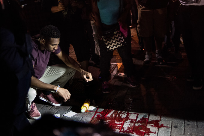 A man looks at blood on the sidewalk.