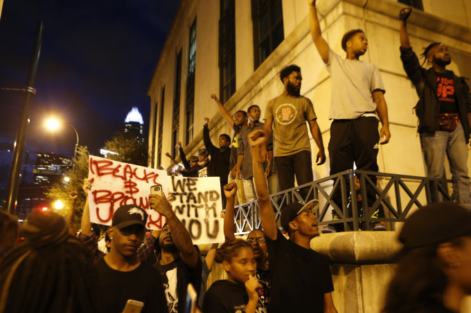 Protesters raise fists outside Charlotte Police department.