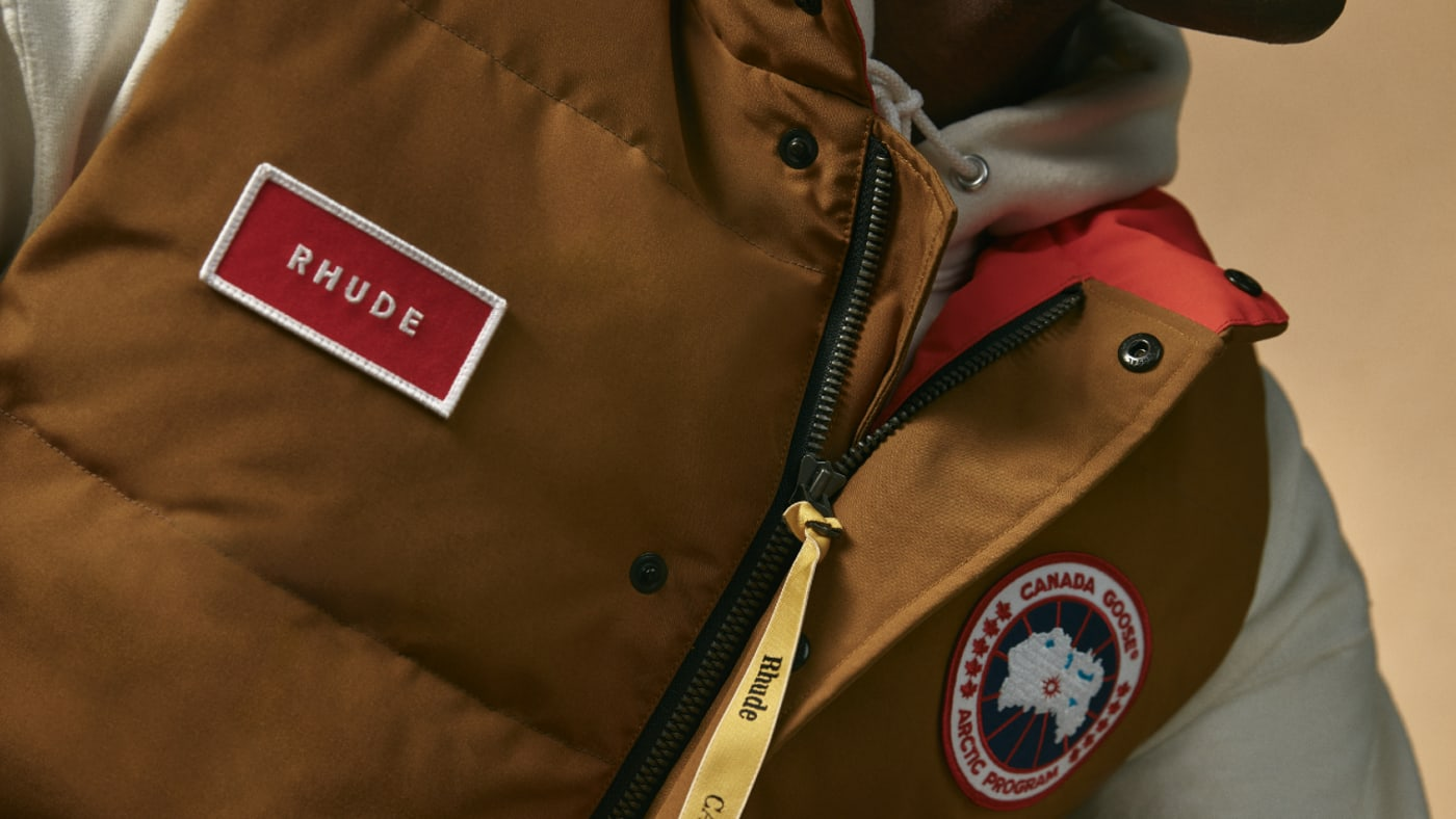 A brown vest worn by a model, with the Canada Goose and RHUDE logos visible