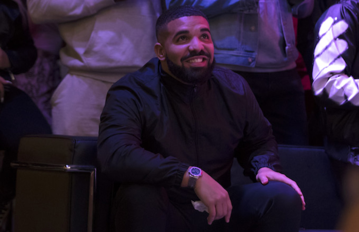 Drake watches a screen alongside other Toronto Raptors fans.