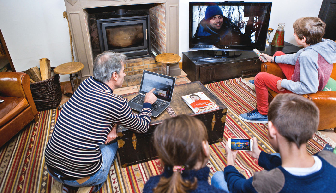 Family in their living room, in front of screens