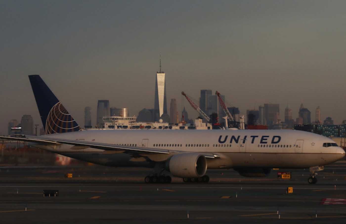 United Airlines airplane passes the skyline of lower Manhattan and One World Trade Center.