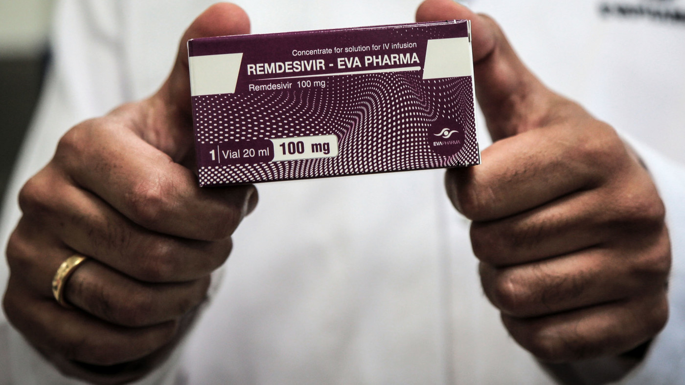 An Egyptian pharmaceutical company employee holds a pack containing vials of Remdesivir.