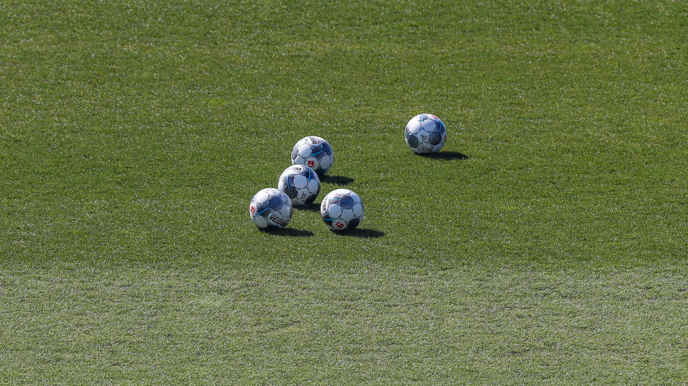 Five balls are lying on the grass of FC Schalke's training facility