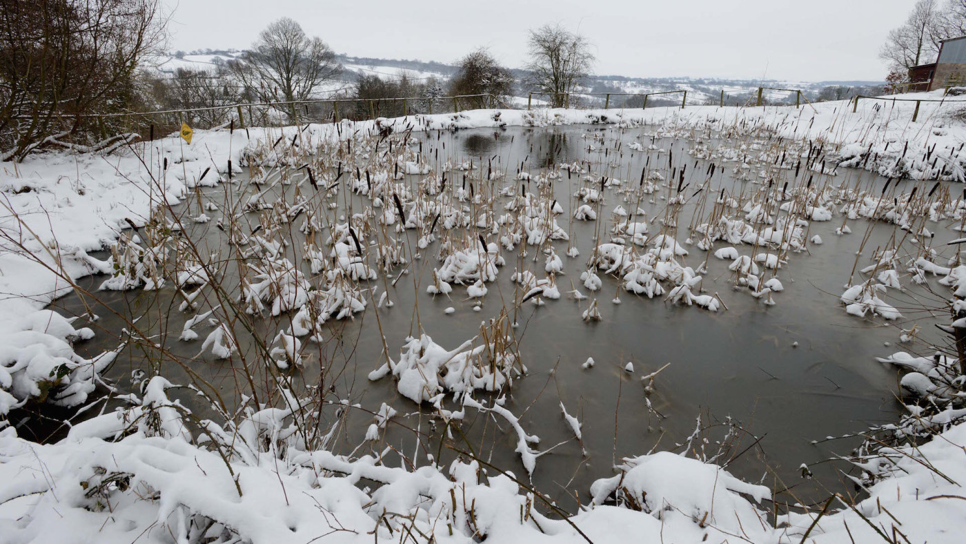 A frozen snow covered pond in the hills