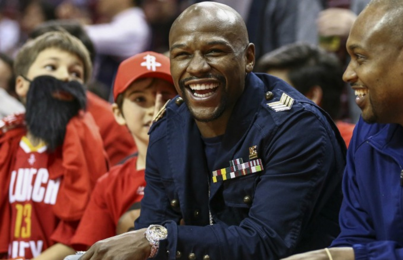 Floyd Mayweather laughs during an NBA game.