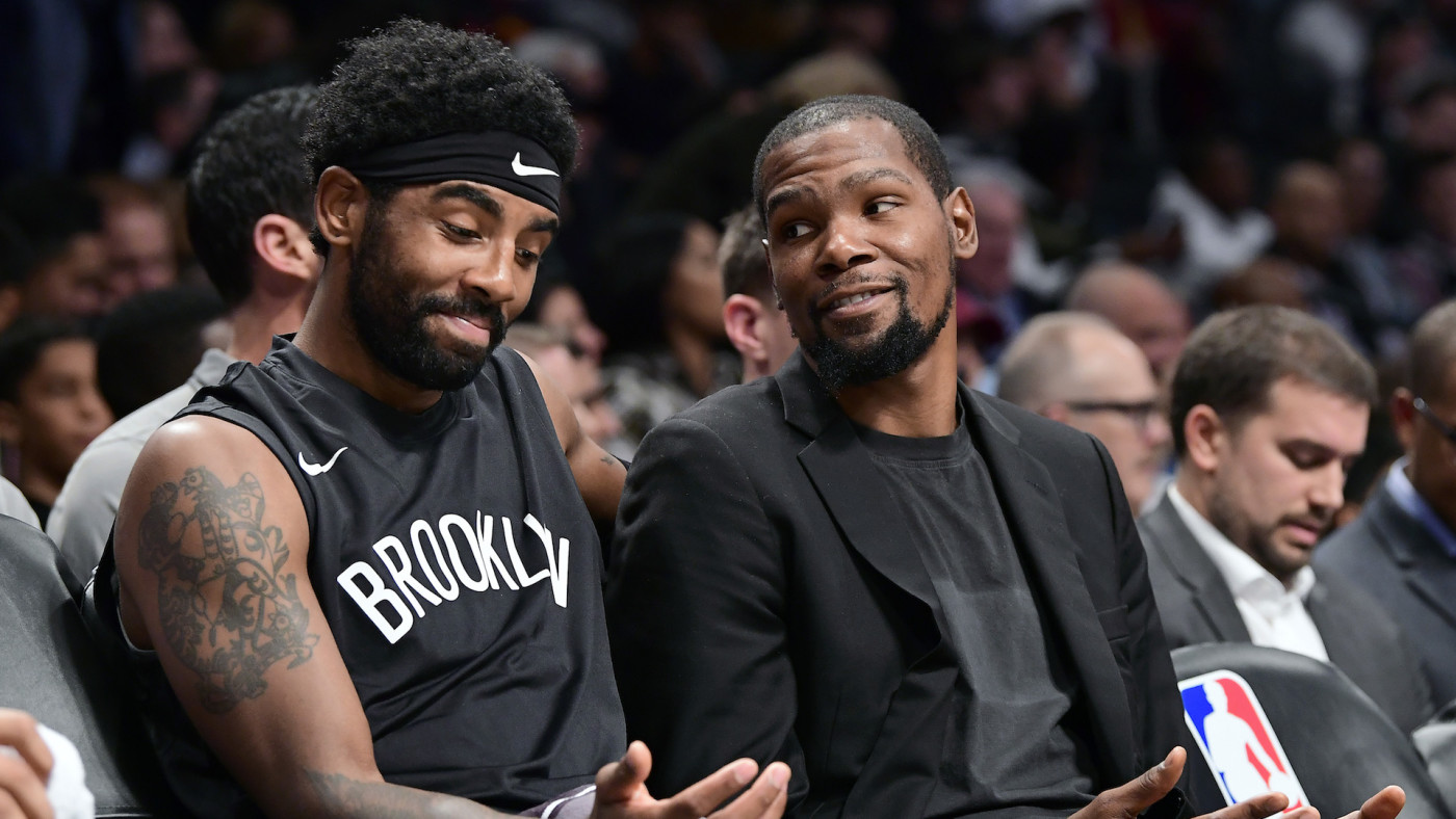 Kyrie Irving #11 and Kevin Durant #7 of the Brooklyn Nets speak on the bench.