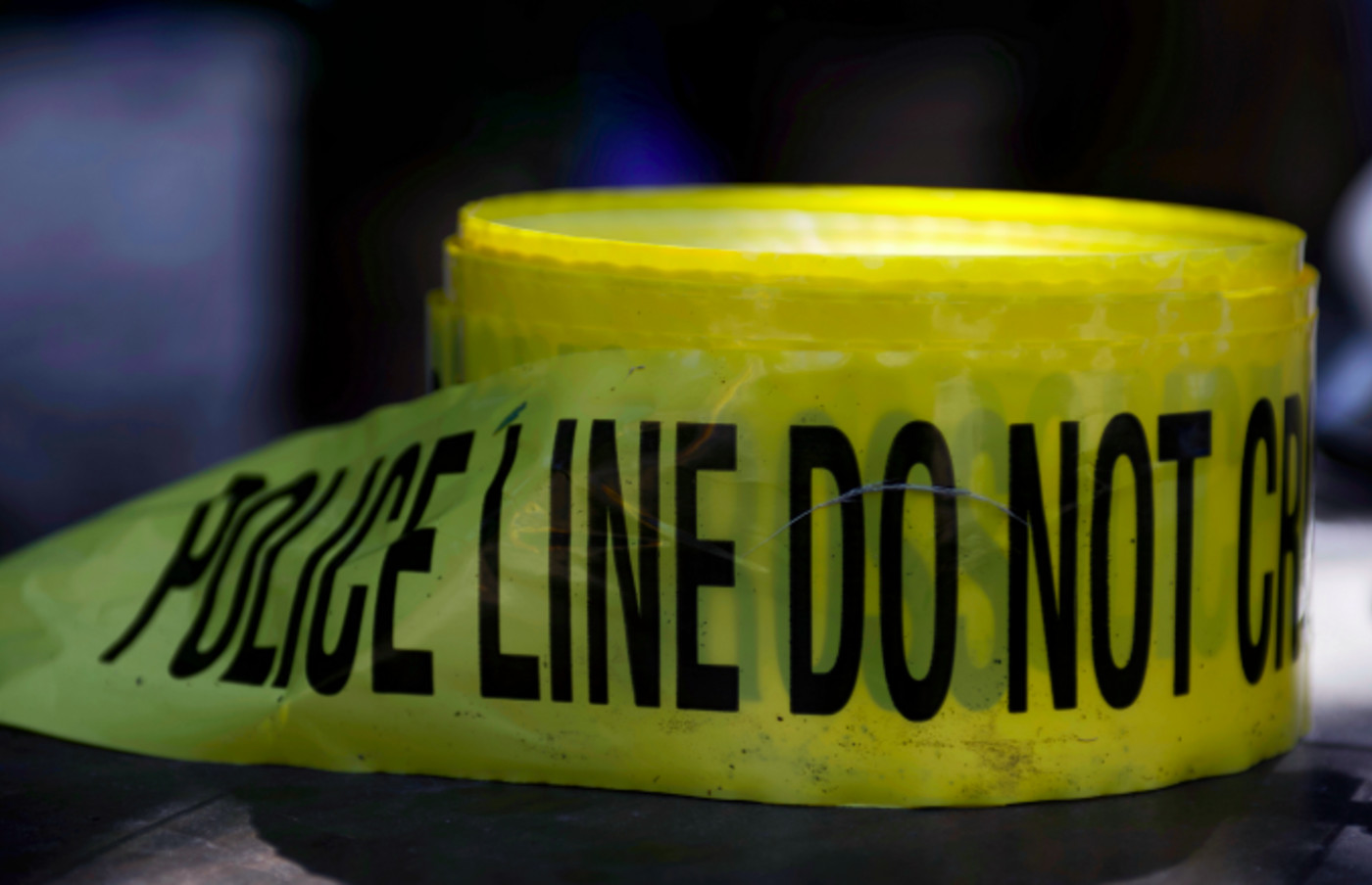 Roll of crime scene tape is unused as police officers