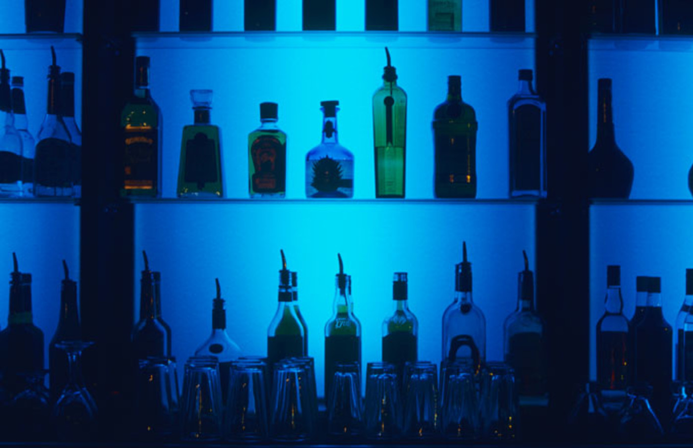 A stock photo of alcohol bottles at a bar.
