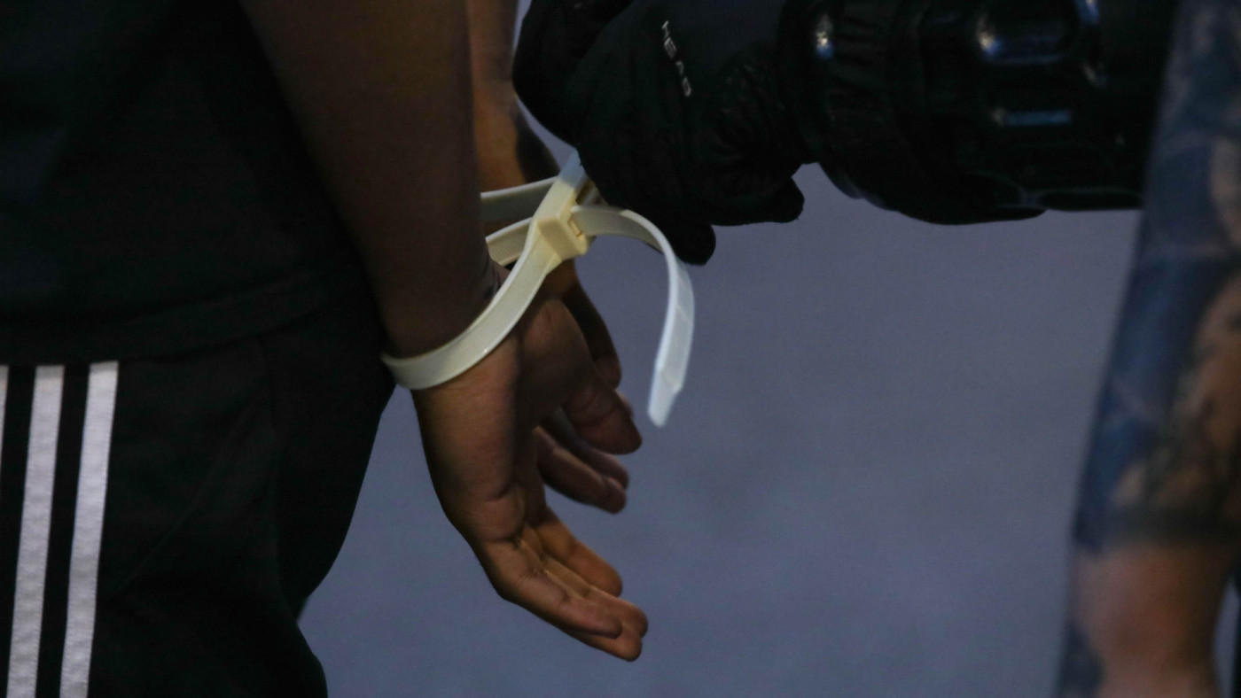 A close up view of a protestor's hands in plastic handcuffs after being arrested