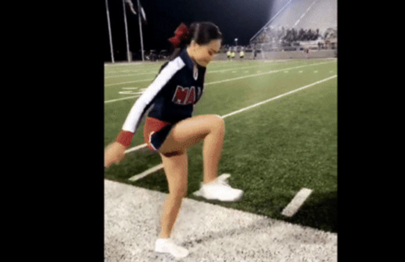 A cheerleader steps on an invisible box.