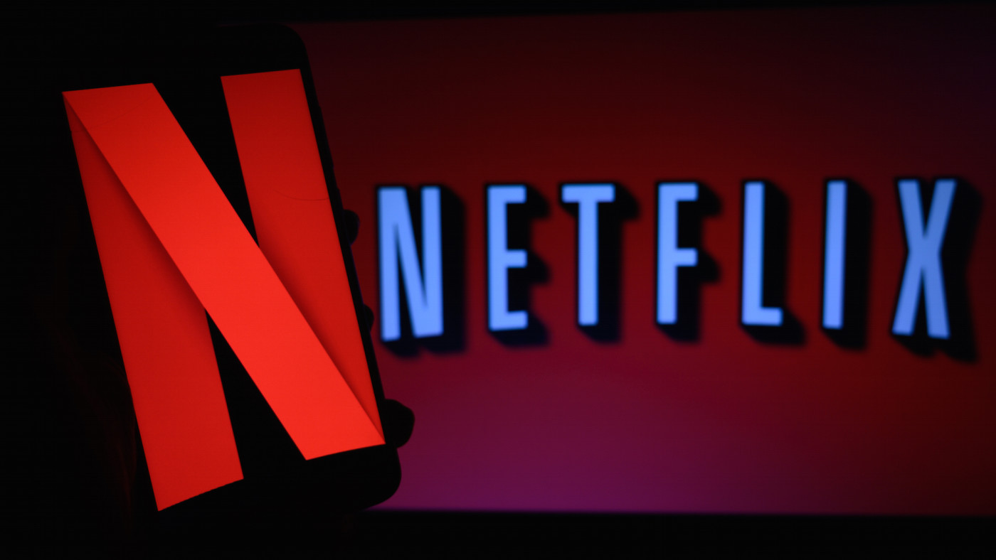 The logo of Netflix is displayed on a laptop screen and on a smart phone screen