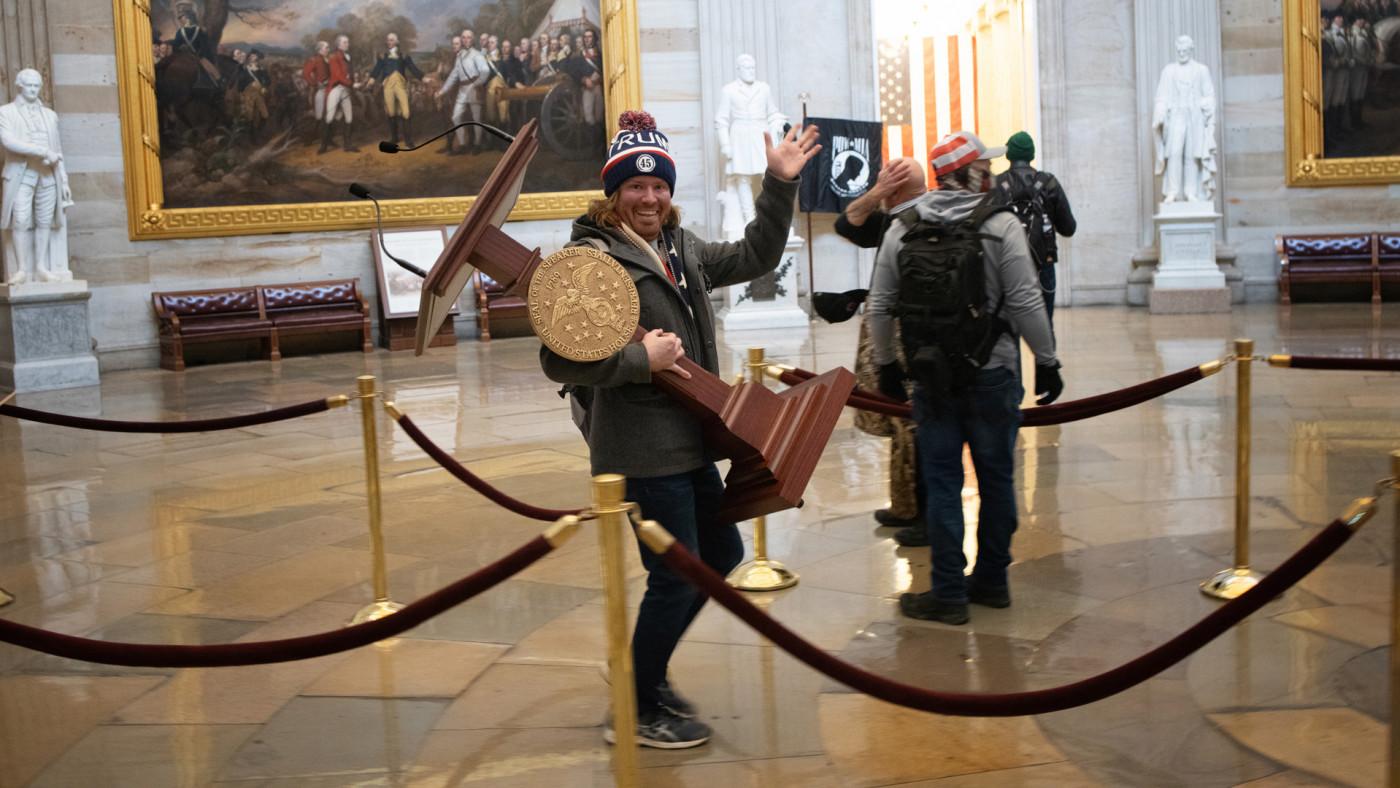 Man holding Nancy Pelosi's lectern in Capitol riots