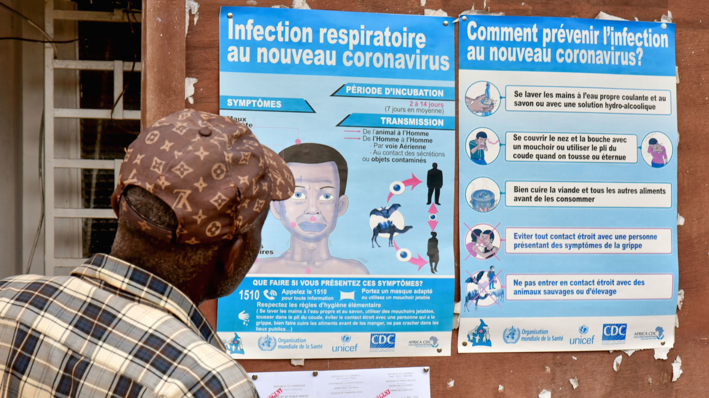 A man watches posters about COVID-19 in Yaounde, Cameroon