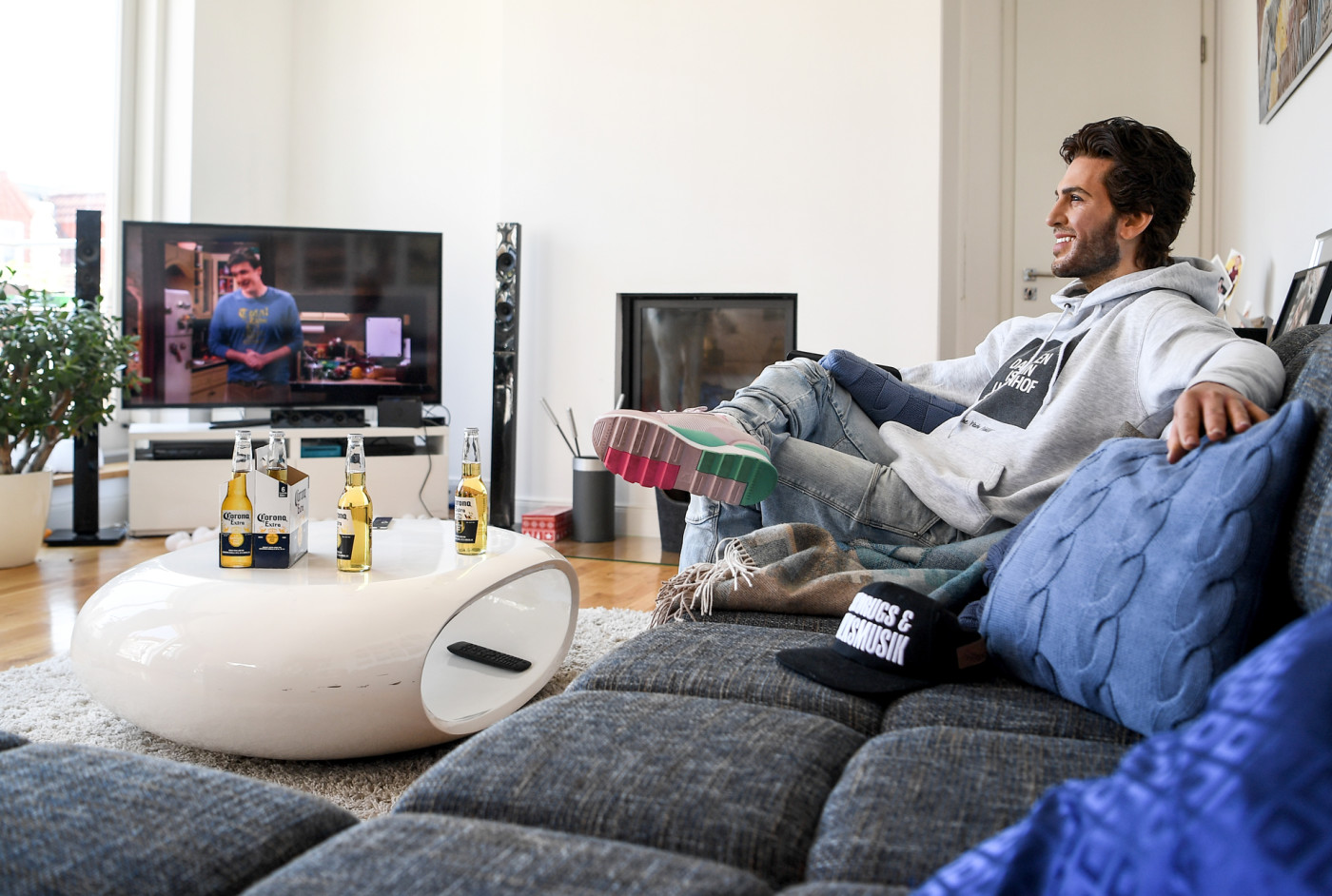 The wax figure of the actor Elyas M'Barek is shown in a scene on a couch while watching television