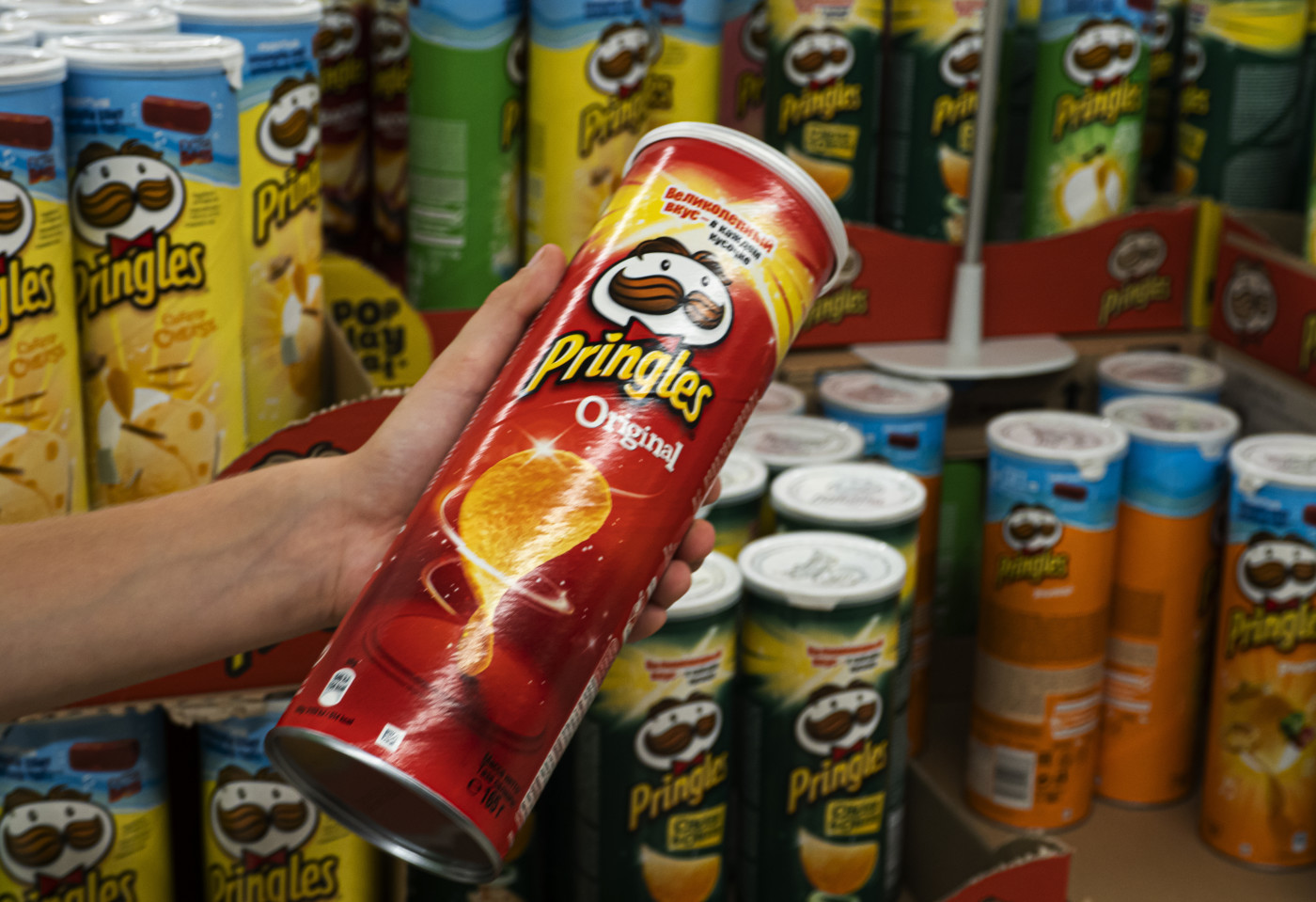 Hand holding original flavored Pringles tube in front of other flavor Pringles tubes