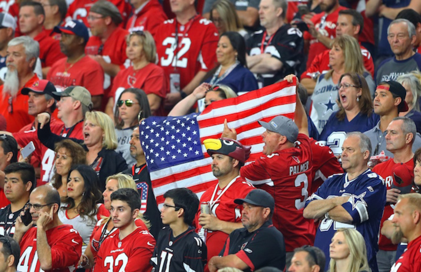 Arizona Cardinals fans hold an american flag.