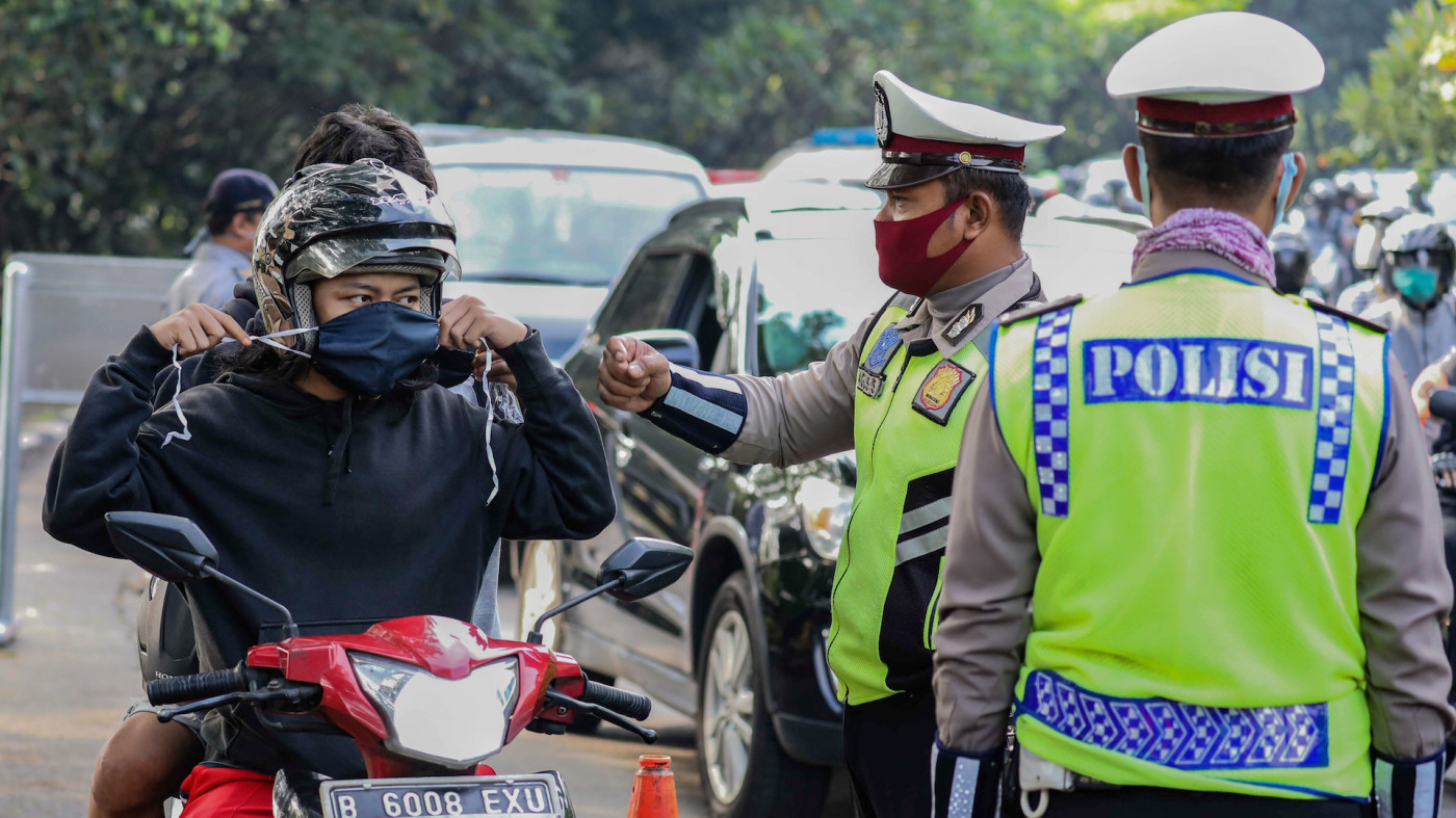 A police officer reminds a motorcyclist to wear his face mask