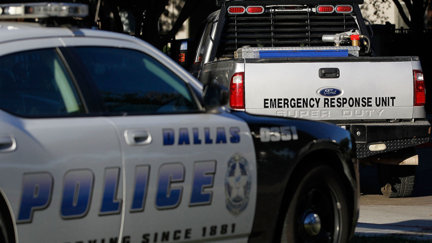 A Dallas police car and an emergency response vehicle sit in the parking lot.