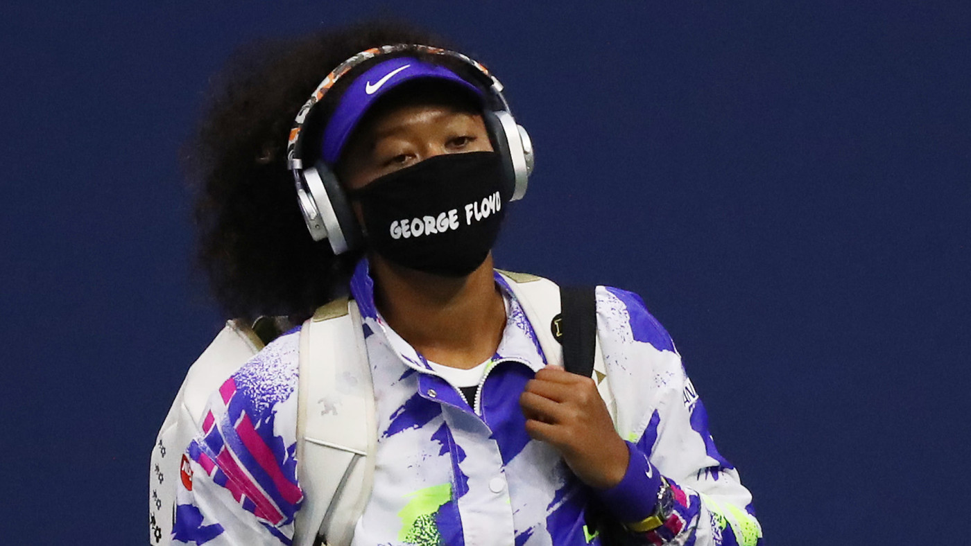 Naomi Osaka walks in wearing a mask with the name of George Floyd on it.