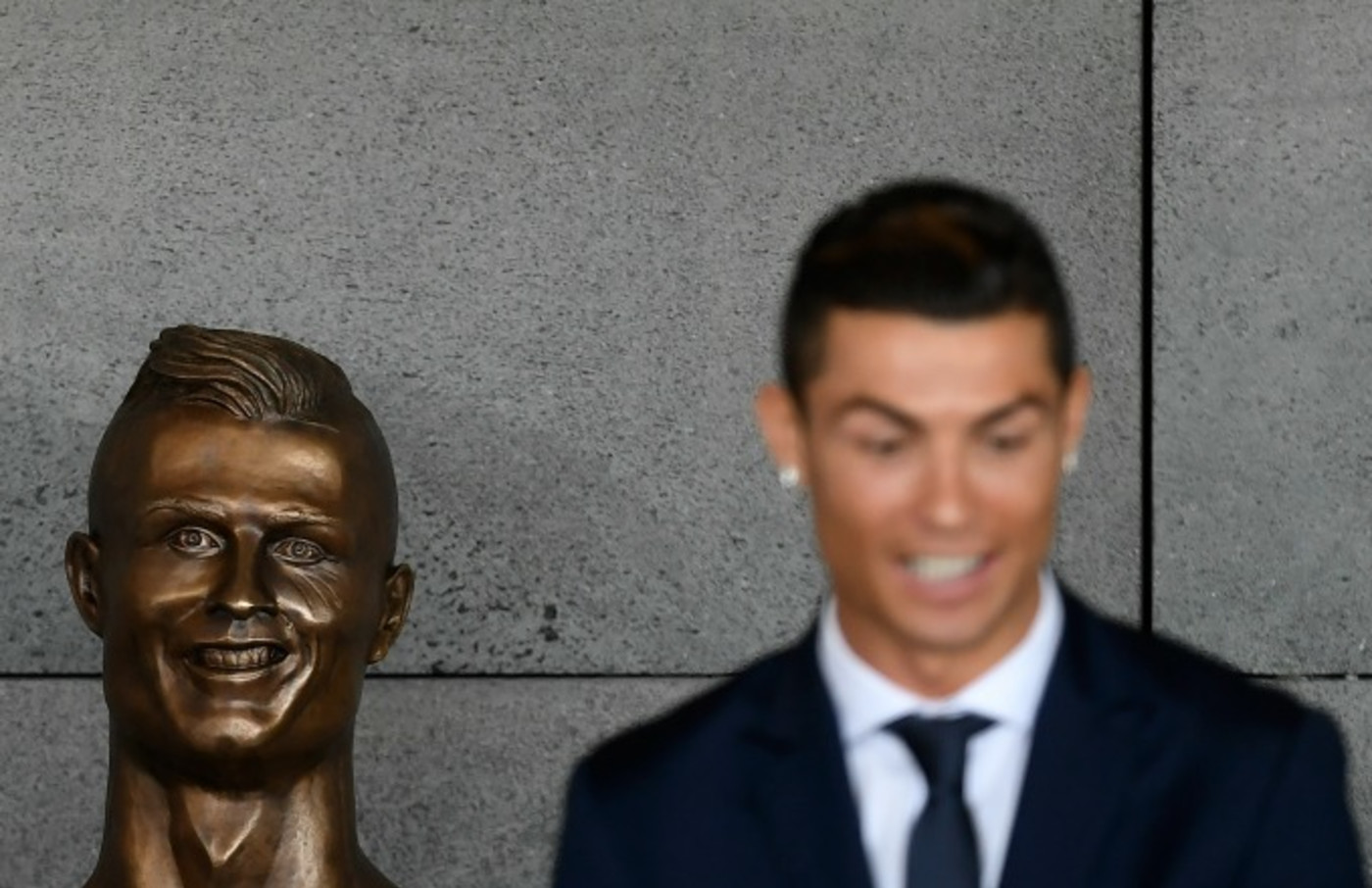 Cristiano Ronaldo stands in front of his statue.