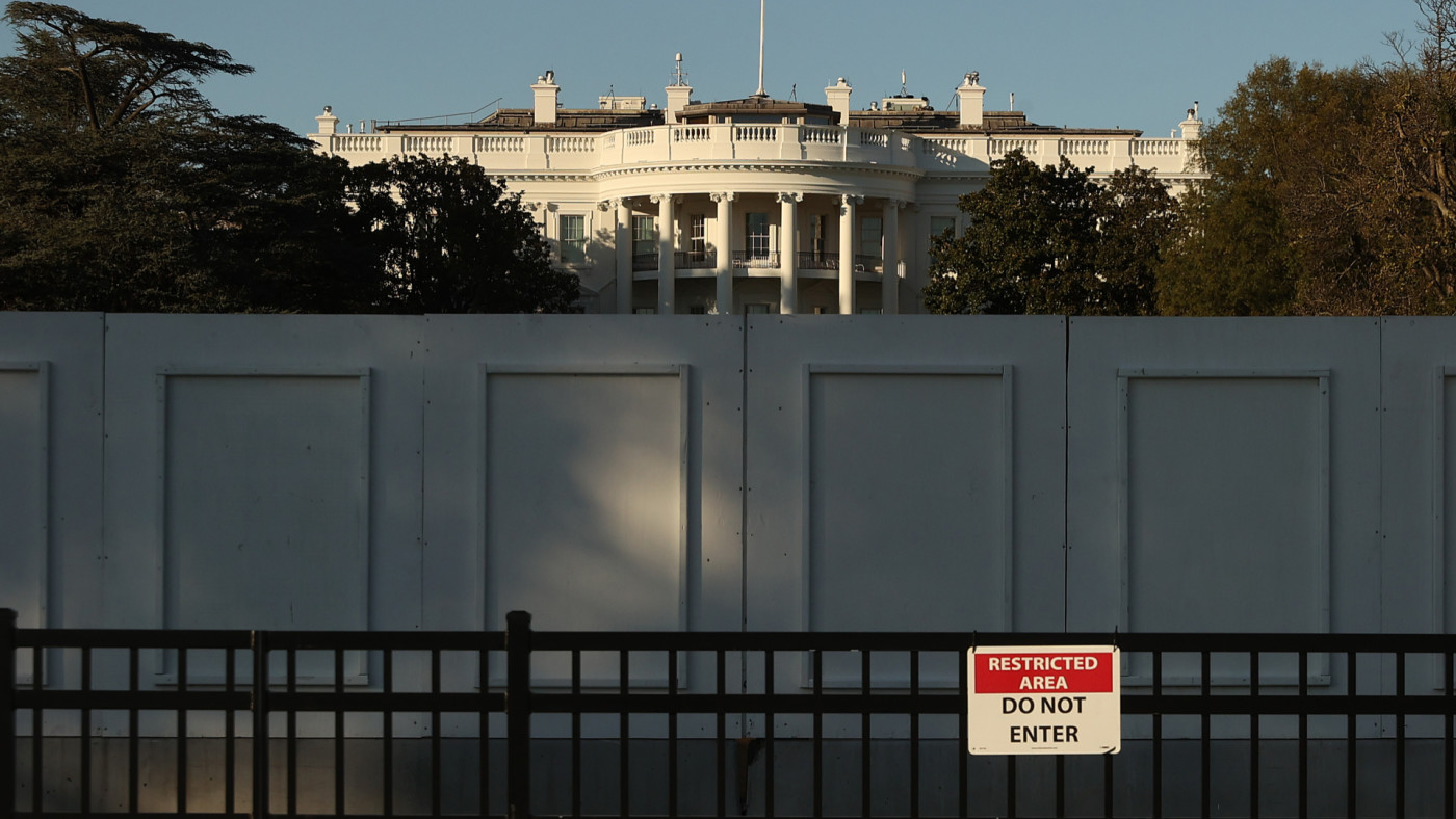 The south side of the White House is seen behind layers of fencing.