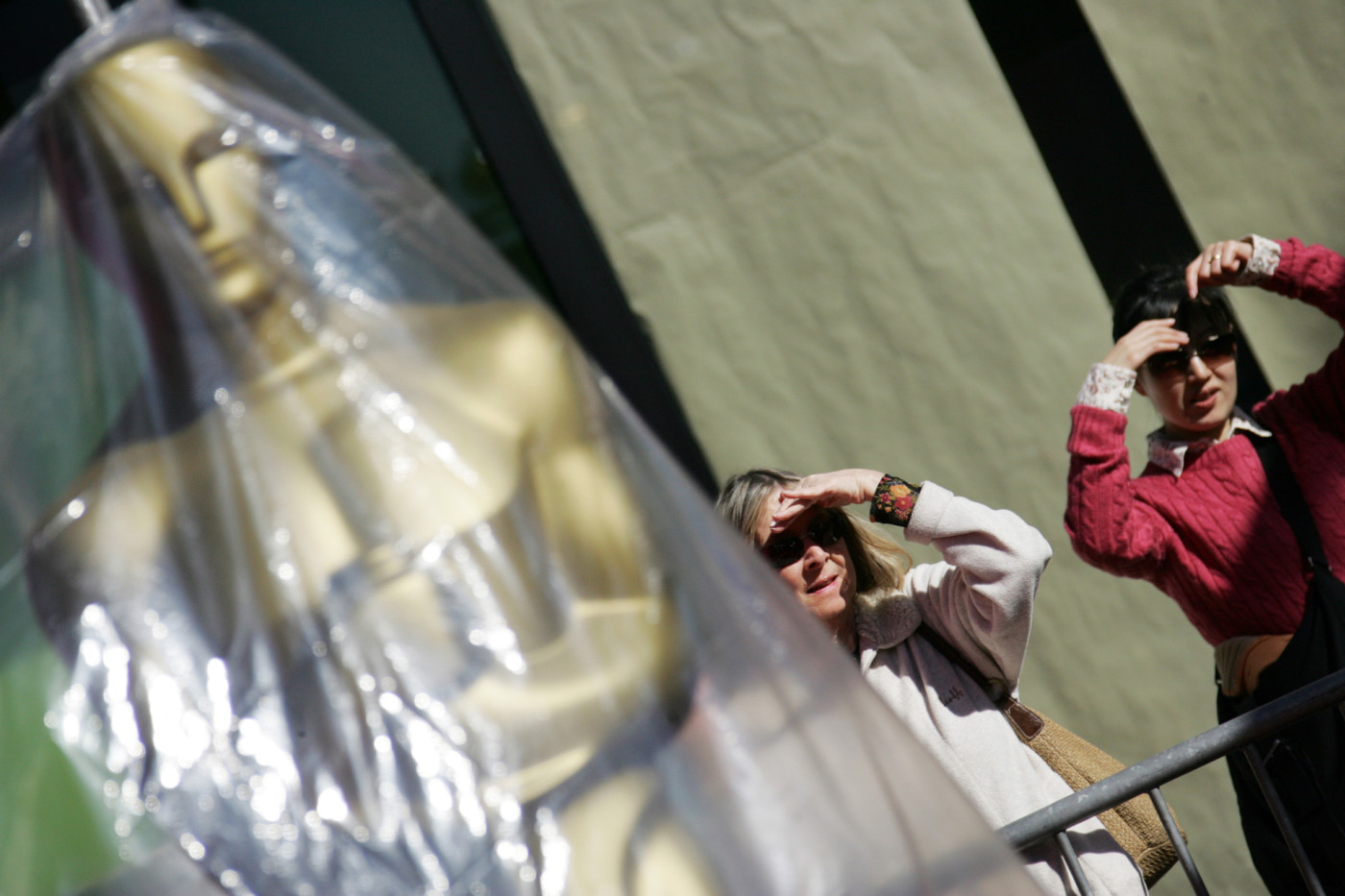 Two women stand next to an Oscar as they watch the Oscar Statues parade