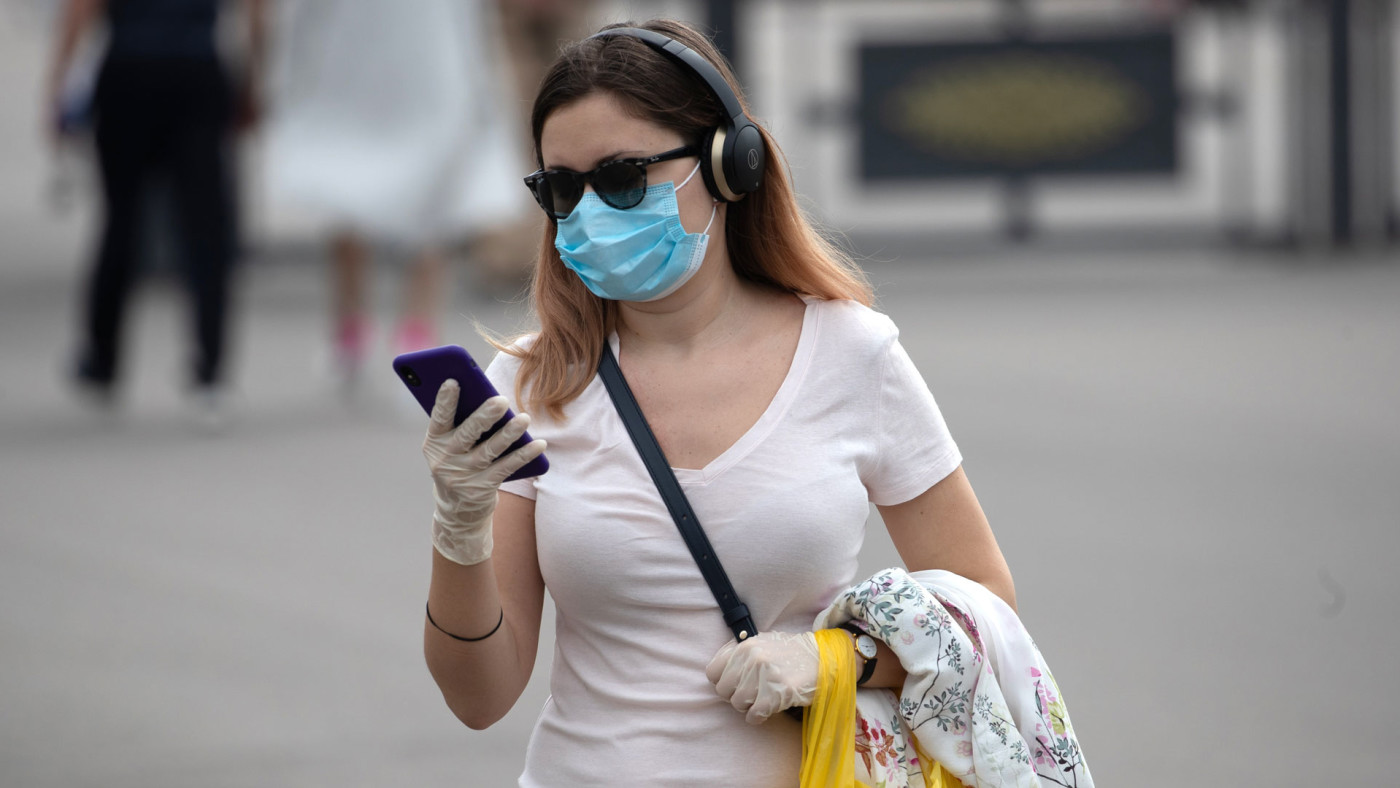 A woman in Moscow stares at her iPhone.