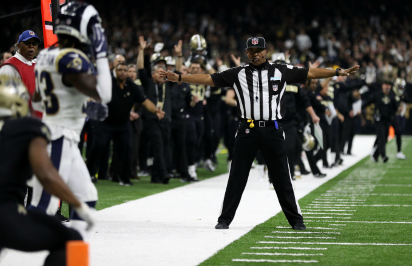 A referee watches as Tommylee Lewis #11 of the New Orleans Saints drops a pass