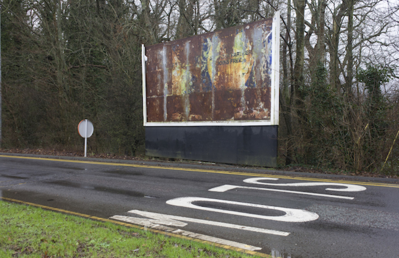 Rusting billboard showing a faded advert landscape at the Reading Services on the M4 motorway