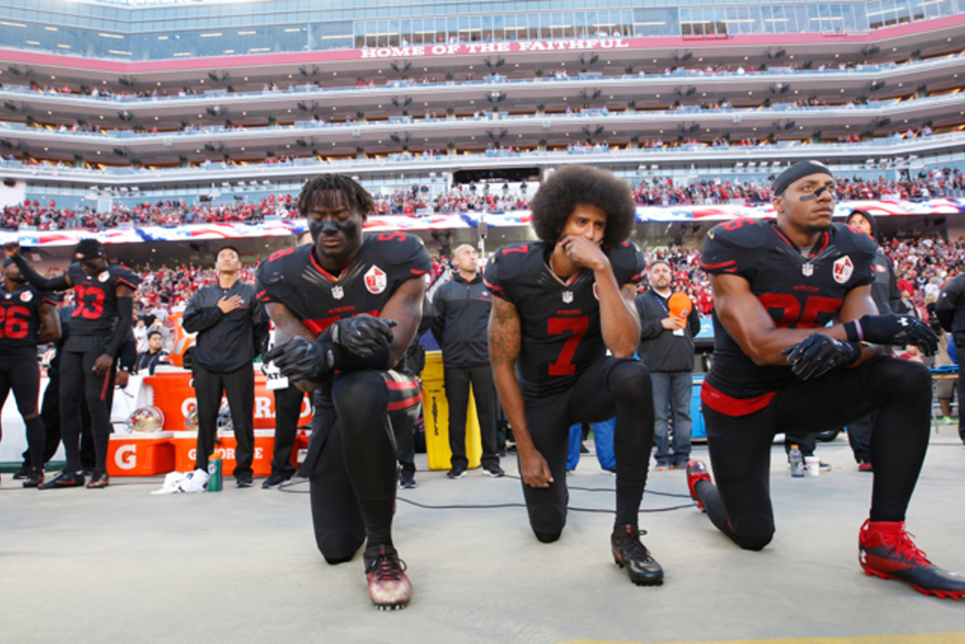 Eli Harold, Colin Kaepernick, and Eric Reid kneel on the sideline