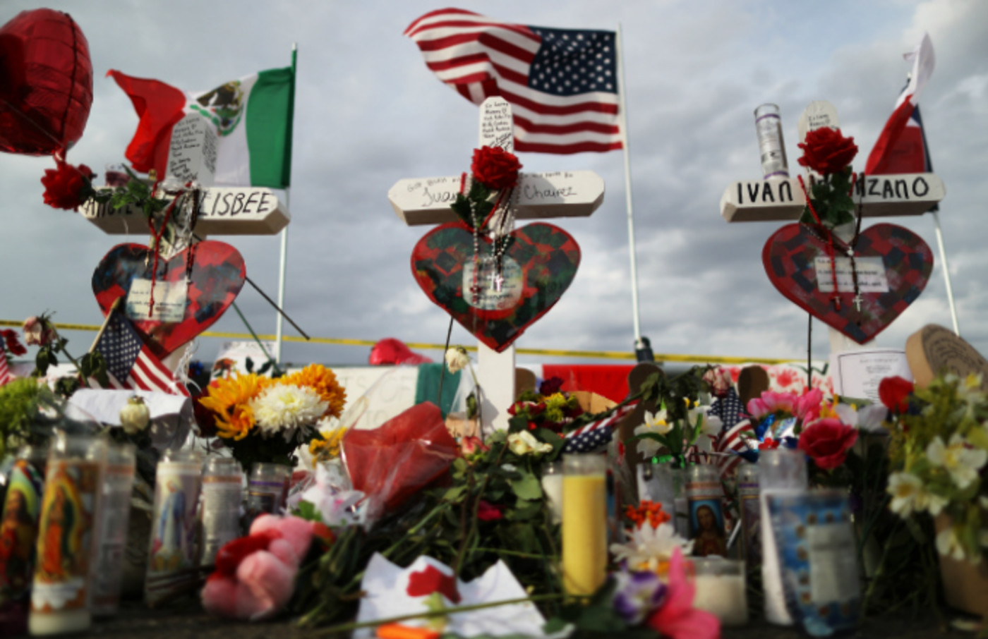 The U.S. and Mexican flags fly above a makeshift memorial for victims