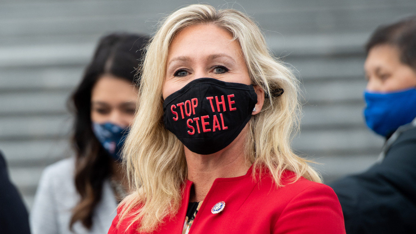 "Marjorie Taylor Greene holds up a ""Stop the Steal"" mask."