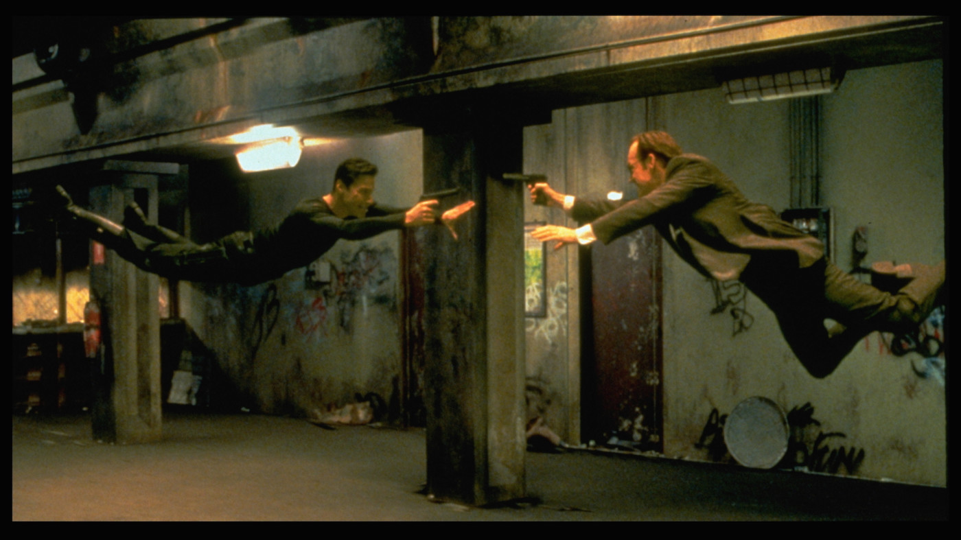 Keanu Reeves and Hugo Weaving face each other in a scene