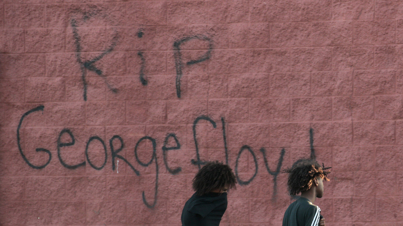 """Two men walk past a wall that has """"RIP George Floyd"""" ."""