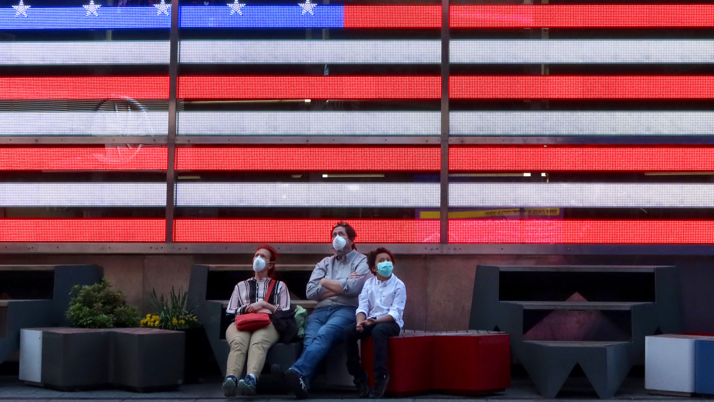 People wear masks as they sit in under an American flag in Times Square .