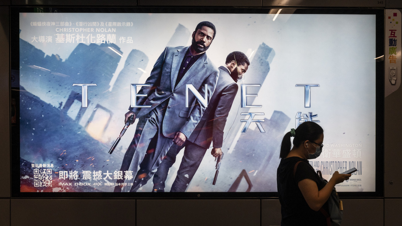 A commuter walks past a poster of Christopher Nolan's blockbuster film Tenet