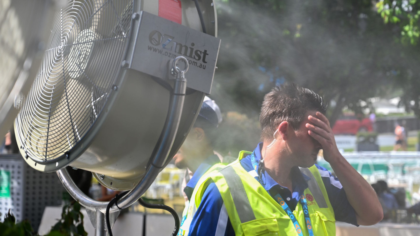 man cools down in front of a mist fan for relief from the hot weather.