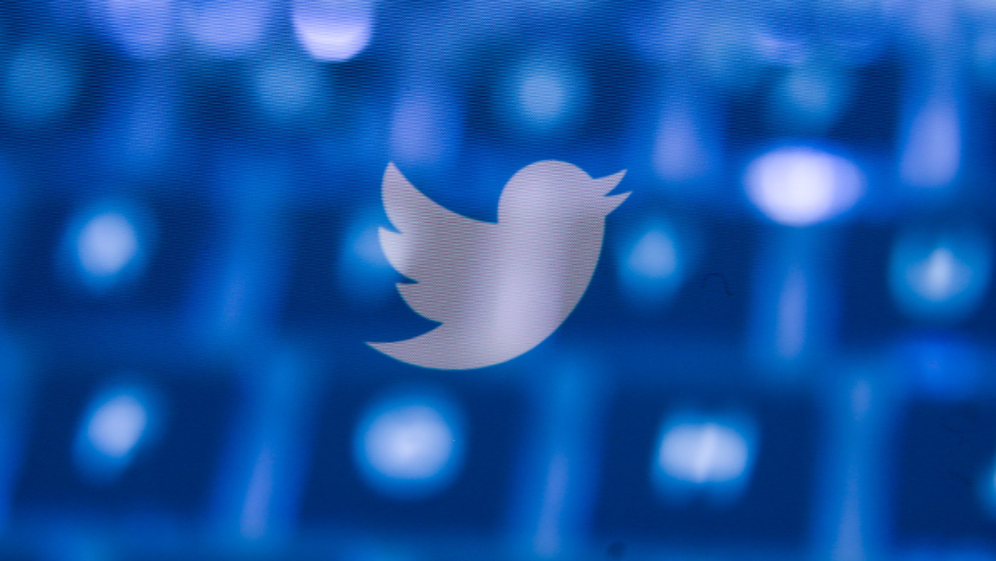 Twitter logo displayed on smartphone and keyboard.