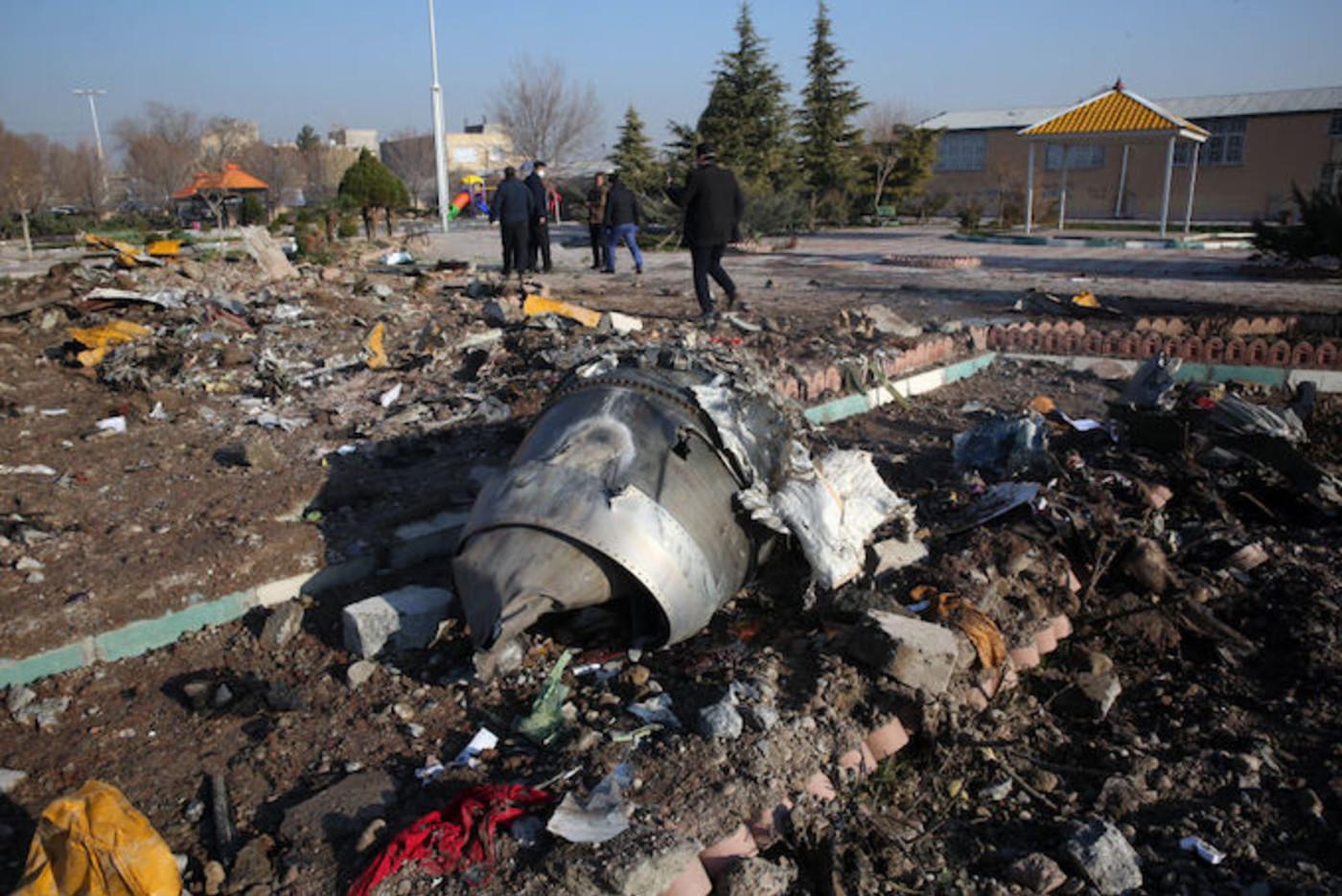 Rescue teams work amidst debris after a Ukrainian plane carrying 176 passengers crashed