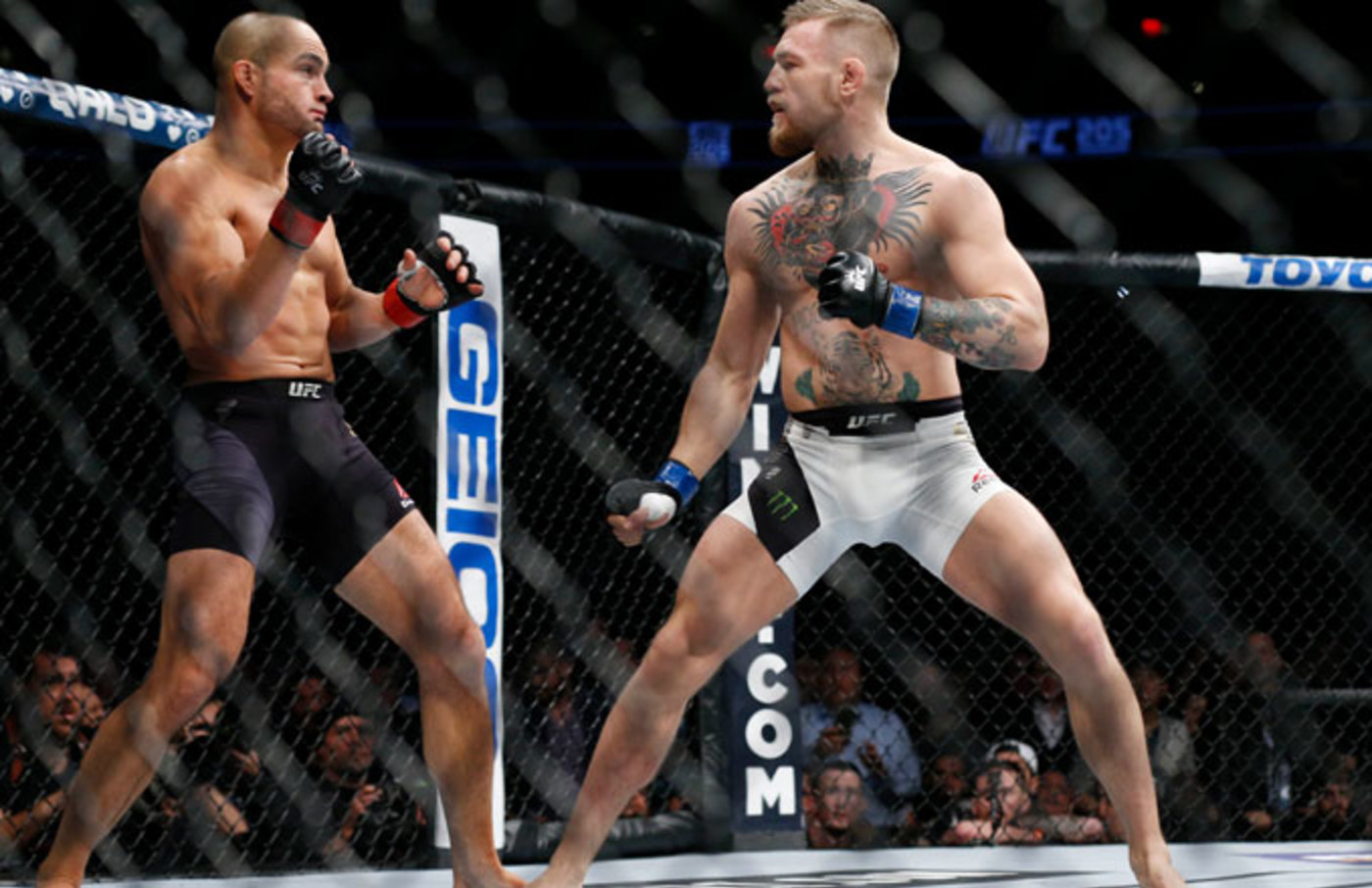 Conor McGregor (blue gloves) fights Eddie Alvarez (red gloves) in their lightweight title bout.