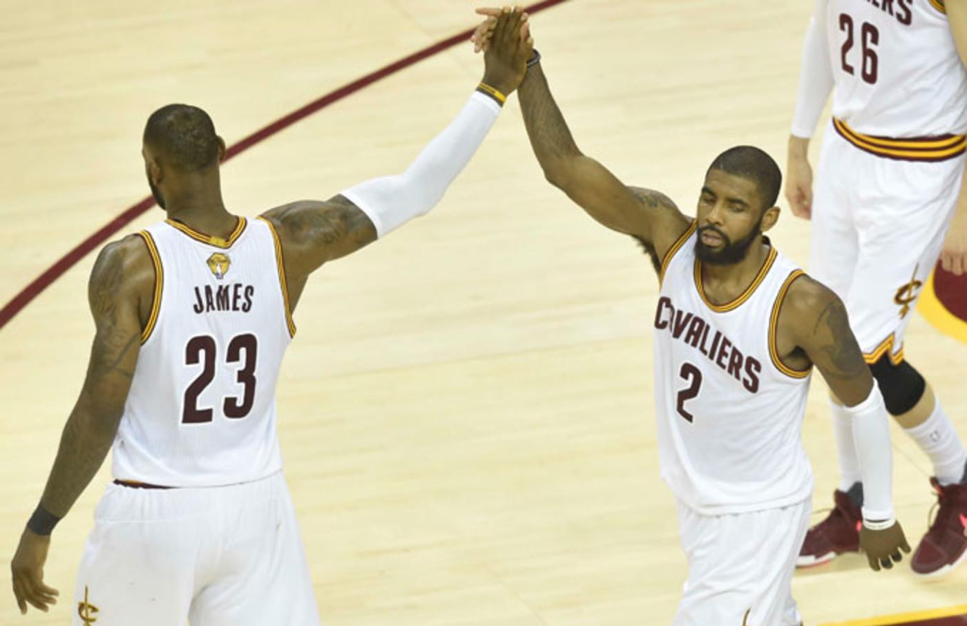 LeBron James high fives Kyrie Irving.